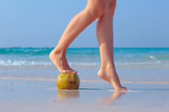 Weibliche Füße gestützt auf Kokosnuss auf Seehintergrund Stockfoto