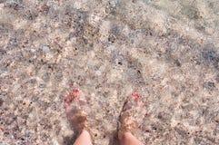 Weibliche Füße im Meer auf einem sandigen Strand Lizenzfreies Stockfoto