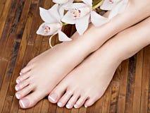 Weibliche Füße mit weißer französischer Pediküre auf Nägeln Am Badekurortsalon Stockfotos