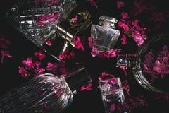 weibliche Flaschen Parfüm mit lila Blumen Lizenzfreies Stockbild
