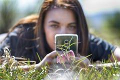 Weibliche Fotografie mit dem Smartphone, der ein Foto der Blume macht Stockbilder