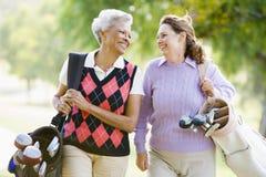 Weibliche Freunde, die ein Spiel des Golfs genießen stockfotos