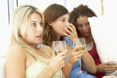 Weibliche Freunde, die einen furchtsamen Film überwachen stockbilder