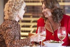 Weibliche Freunde, die an einer Gaststätte zu Abend essen Lizenzfreie Stockfotos
