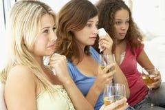 Weibliche Freunde, die zusammen einen traurigen Film überwachen Stockfotografie