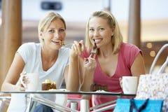 Weibliche Freunde, die zusammen am Mall zu Mittag essen Stockfotos