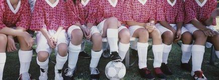 Weibliche Fußball-Spieler, die nebeneinander sitzen Lizenzfreie Stockbilder