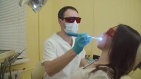 Weibliche geduldige erhaltene Behandlung mit zahnmedizinischer UV-Licht-Ausrüstung Zahnmedizinisches Büro stock footage