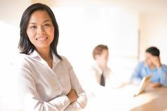 Weibliche Geschäftsfrau-lächelnde Sitzung stockfoto
