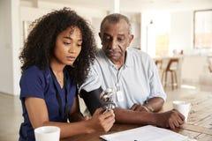 Weibliche Gesundheitswesenarbeitskraft, die den Blutdruck eines älteren Mannes während eines Hausbesuchs überprüft stockfoto