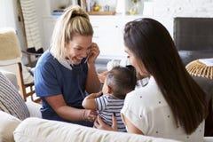 Weibliche Gesundheitswesenarbeitskraft, die zu Hause eine junge Mama und ihren Säuglingssohn, unter Verwendung des Stethoskops be stockfotos