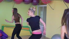 Weibliche Gruppe mit dem Training, das flexible Aerobic in einer modernen Turnhalle 4k tut stock video