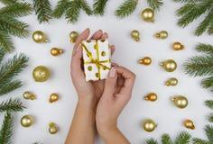 Weibliche Hände öffnet eine kleine Geschenkbox auf weißem Hintergrund mit goldenen Weihnachtsbällen und grünen Tannenzweigen Wint Stockbilder