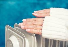 Weibliche Hände über der Heizung lizenzfreie stockbilder