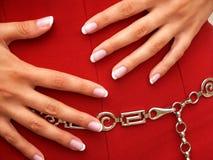 Weibliche Hände auf rotem Rock stockbild