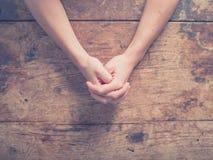 Weibliche Hände bei Tisch gefaltet stockfotos