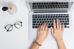 Weibliche Hände benutzen Laptoptastatur auf weißer Tabelle lizenzfreies stockbild