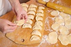 Weibliche Hände bereiten traditionelle Mehlklöße zu Stockbilder