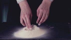 Weibliche Hände brechen das Ei in Mehl für die Herstellung des Teigs über schwarzer Tabelle Dunkle rustikale Art Im Retro- Filter stock footage