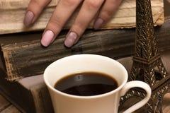 Weibliche Hände, coffe Schale und alte Bücher Stockbild