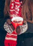 Weibliche Hände in den Handschuhen, die eine Tasse Tee halten Lizenzfreies Stockfoto