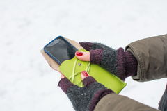 Weibliche Hände in den Handschuhen, die Smartphone halten Lizenzfreie Stockfotografie