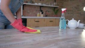 Weibliche Hände in den Handschuhen mit dem Lappen, der leicht Tabelle vom Staub und Flecke mit Reinigungsmittel an der Küche s stock footage
