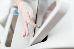 Weibliche Hände in den Polyäthylenhandschuhen, die den Schirm von Laser-Apparat berühren, um ihn einzuschalten Kein Gesicht Nahau stockfotos