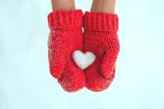 Weibliche Hände in den warmen roten gewirkten Handschuhen mit schneebedecktem Herzen Whi Lizenzfreies Stockfoto
