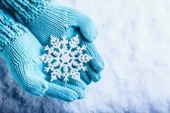 Weibliche Hände in der hellen Knickente strickten Handschuhe mit funkelnder wunderbarer Schneeflocke auf einem weißen Schneehinte
