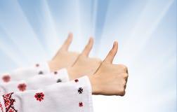 Weibliche Hände in der ukrainischen nationalen Kleidung zeigt Symbol-O.K. Stockfotografie