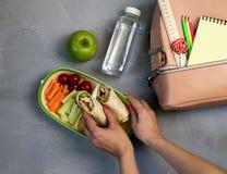 Weibliche Hände, die Abendessen im Lunchbox auf grauer Tabelle verpacken lizenzfreies stockbild