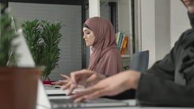 Weibliche Hände, die auf der Tastatur, Nahaufnahme schreiben Mädchen im rosa hijab im Hintergrund Büro, Geschäft, Arbeit, Frauen stock video