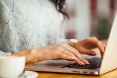Weibliche Hände, die auf einem Laptop schreiben lizenzfreie stockfotos