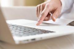 Weibliche Hände, die auf einem Laptop trackpad schreiben stockbilder
