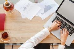Weibliche Hände, die auf Laptoptastatur schreiben Papier mit Diagrammen lizenzfreie stockbilder