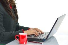 Weibliche Hände, die auf Laptoptastatur am Schreibtisch lokalisiert auf weißem Hintergrund schreiben Lizenzfreies Stockfoto