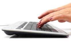 Weibliche Hände, die auf Tastatur schreiben Stockfotos