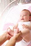 Weibliche Hände, die Babyfüße halten Stockfotos