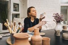 Weibliche Hände, die an Becher arbeiten Lizenzfreie Stockfotografie
