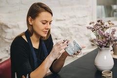 Weibliche Hände, die an Becher arbeiten Stockfoto