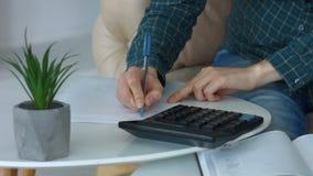Weibliche Hände, die Berechnungen auf Taschenrechner machen stock footage