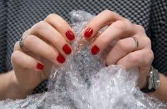 Weibliche Hände, die Blasen in der Luftpolsterfolie knallend Stockfotografie