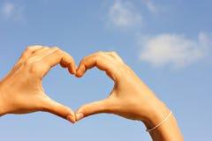 Weibliche Hände, die das Herz auf dem Himmelhintergrund machen stockbilder