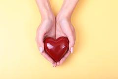 Weibliche Hände, die das rote Herz, lokalisiert auf Goldhintergrund geben Stockbilder