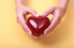 Weibliche Hände, die das rote Herz, lokalisiert auf Goldhintergrund geben Lizenzfreie Stockfotos