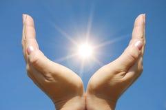 Weibliche Hände, die den Sun berühren Lizenzfreie Stockbilder