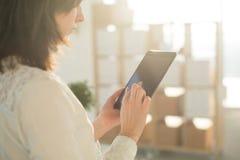 Weibliche Hände, die den Tabletten-PC, schreibend, unter Verwendung des mit Berührungseingabe Bildschirms und Wi-Fiinternets halt Lizenzfreies Stockfoto