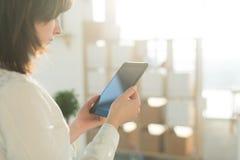 Weibliche Hände, die den Tabletten-PC, schreibend, unter Verwendung des mit Berührungseingabe Bildschirms und Wi-Fiinternets halt Stockfoto
