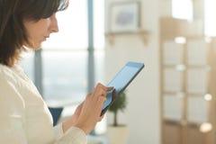 Weibliche Hände, die den Tabletten-PC, schreibend, unter Verwendung des mit Berührungseingabe Bildschirms und Wi-Fiinternets halt Lizenzfreie Stockfotografie